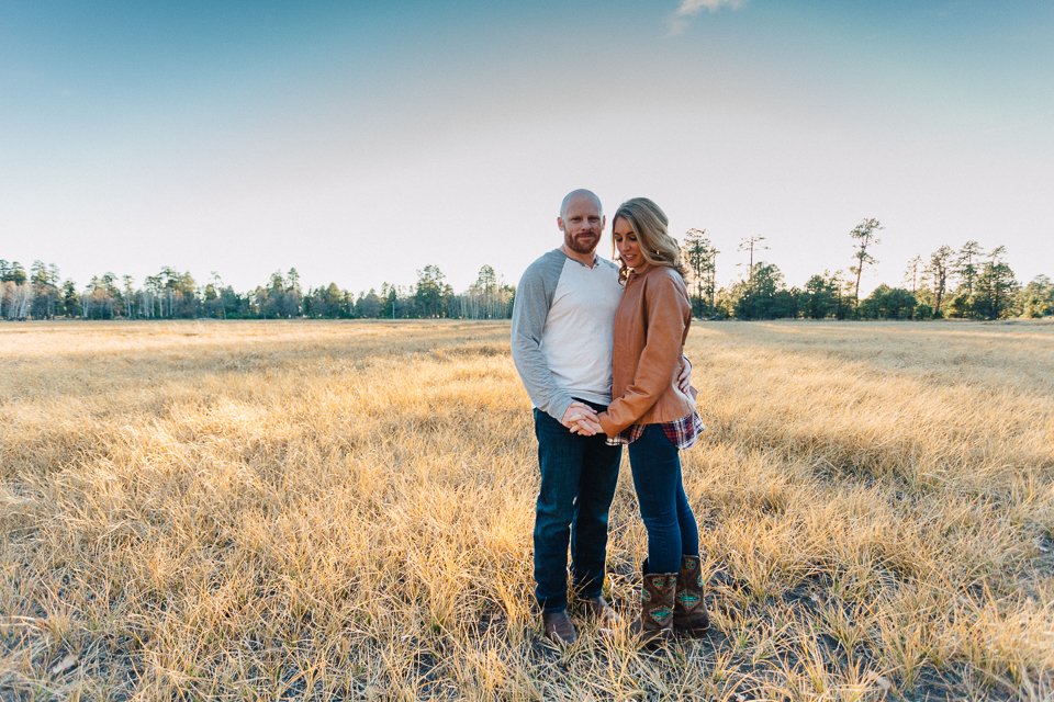 Sunset photo of a couple standing in a field.