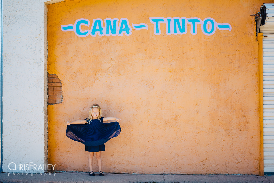 Little girl holding up her blue dress for family pictures at the Phoenix Zoo.