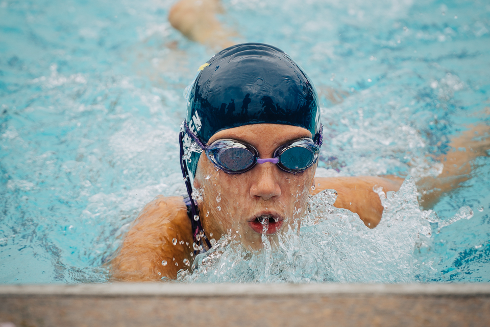 Young swimmer finishes her 50 yard freestyle swim heat.