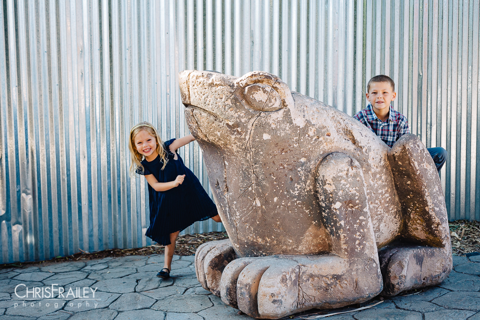 Children playing on a stone frog statue for family pictures at the Phoenix Zoo.