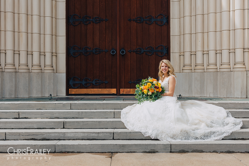 Bride sitting on stone steps posing in front of a church in Fort Worth Texas.