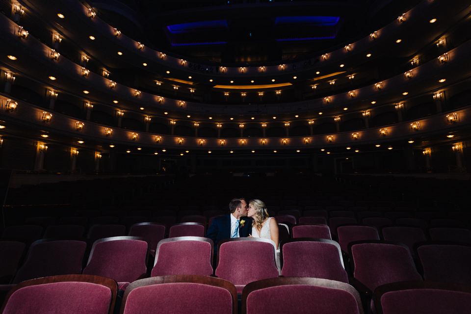 Bride and groom kissing in theater seats of Bass Hall.