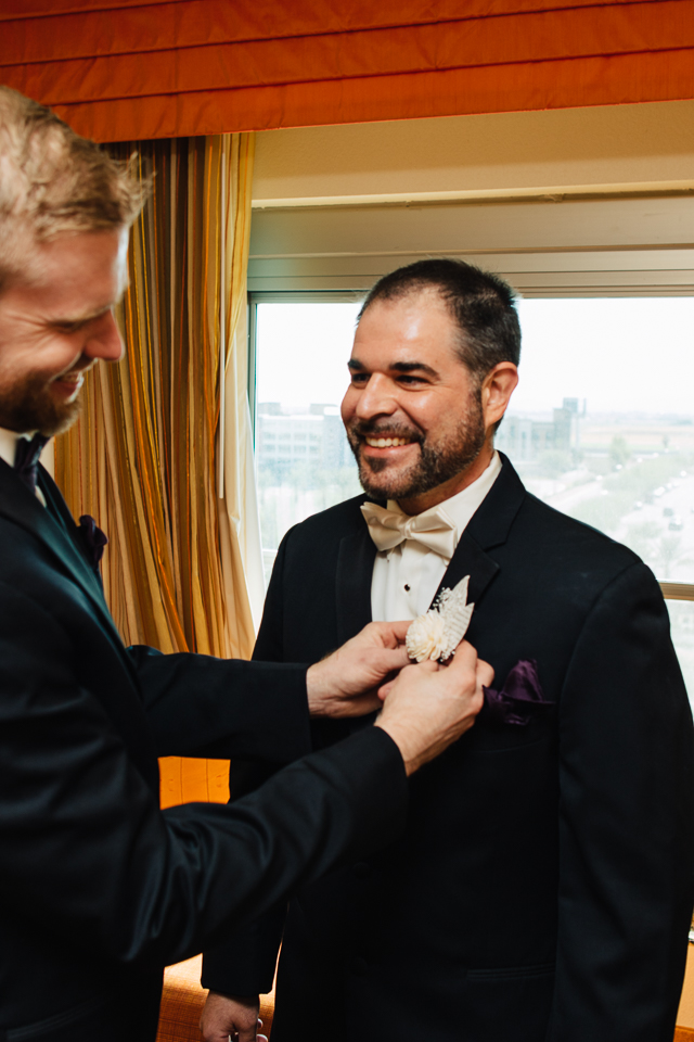 Best man helping groom with his jacket.