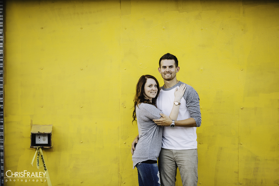 Couple standing in front of a yellow wall during their engagement shoot at Roosevelt Row. .