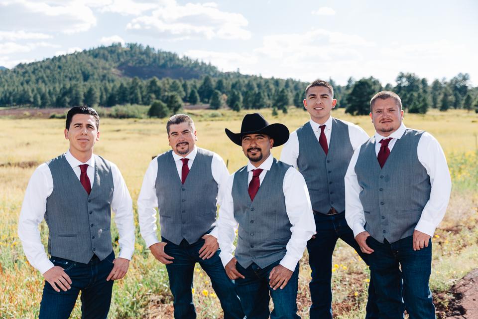 Groom posing with groomsmen in a meadow.