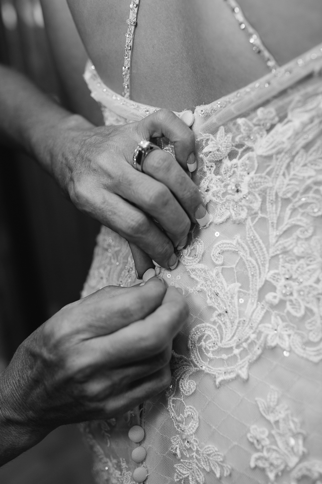 Mother of bride helping button up bride's wedding dress.