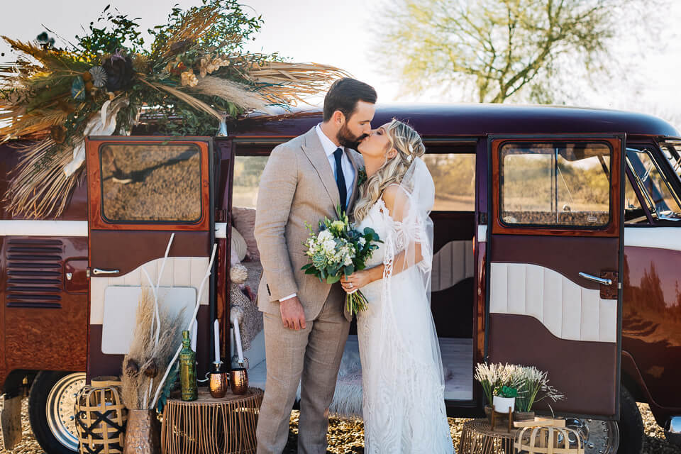 Bride and groom kissing outside a decorated VW bus.