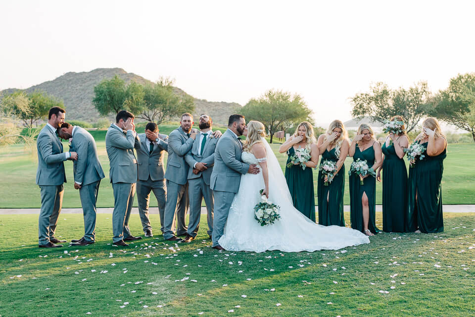 Bridal party looking away while wedding couple kiss.